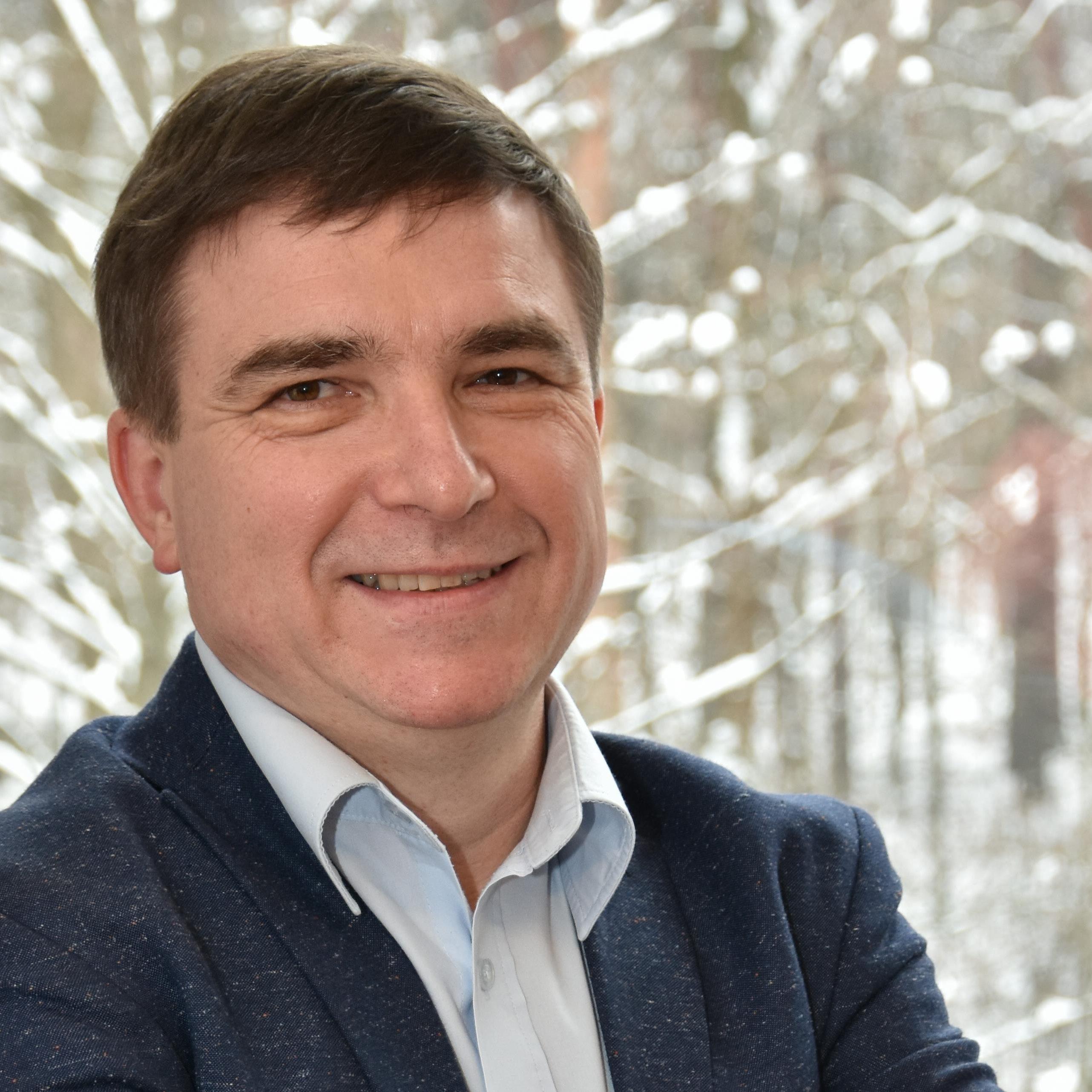 Uśmiechnięty Tomasz Kowalik doświadczony coach prowokatywny